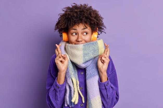 巻き毛の髪の喜んでアフロアメリカ人の女性が指を交差させて幸運を信じて首の周りに暖かい冬のスカーフを着用し、ヘッドフォンでお気に入りの音楽を聴きます。