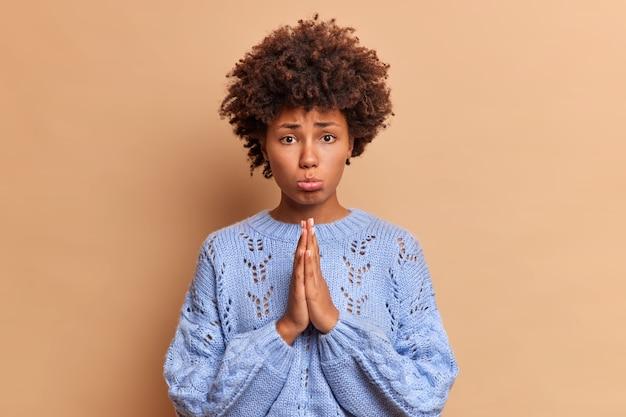 Donna triste dai capelli ricci che stringe le labbra tiene i palmi premuti insieme e guarda infelicemente implorante davanti chiede scuse ha bisogno di aiuto posa sul muro marrone si sente in colpa per aver fatto qualcosa di sbagliato