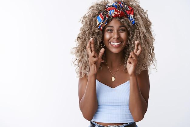 縮れ毛の女性アフロヘアスタイル、夢が叶うと信じて、彼女の側に幸運を感じ、幸運を指で交差させ、笑顔で、祈り、そして願いが叶うことを期待する