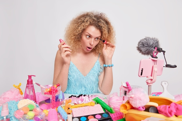 La donna dai capelli ricci applica il mascara registra il video in streaming live dà consigli su come truccarsi per il suo vlog circondato da diversi prodotti cosmetici isolati sul muro bianco. vlogger di bellezza