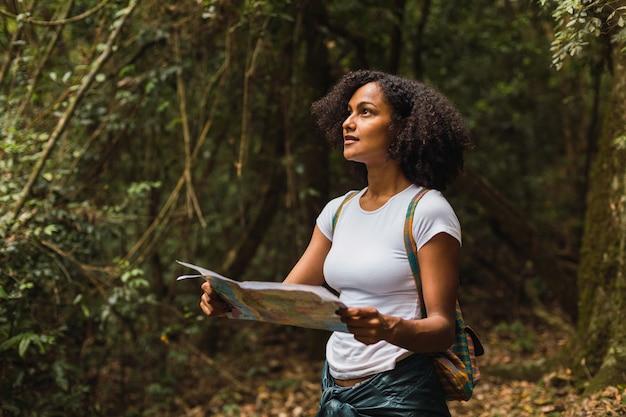 地図を持っている縮れ毛の女性、森の観光客-白いシャツを着て、紙の地図、ジャングルの背景を持って見ている若いブルネット。
