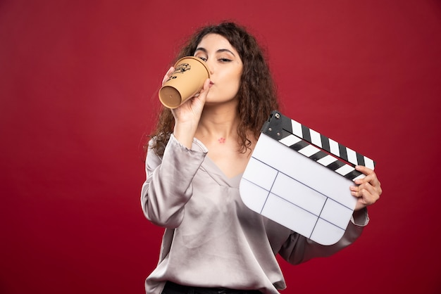 Curly haired woman holding clapperboard and drinking coffee.