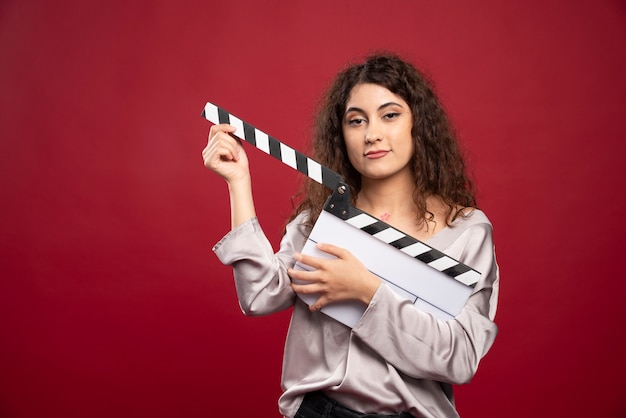 Curly haired woman holding clapperboard.