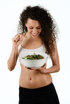 Curly-haired woman holding a salad