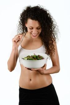 Donna dai capelli ricci in possesso di un insalata
