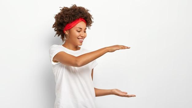 Кудрявая женщина показывает рост чего-то, жестикулирует обеими руками, демонстрирует размер упаковки