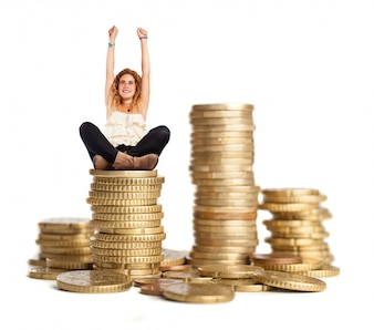 Curly-haired woman sitting on a pile of coins