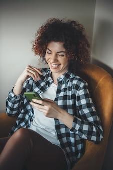 Кудрявая женщина, улыбаясь в кресле, переписывается по телефону дома во время учебы удаленно