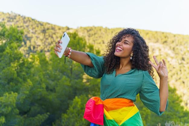 携帯電話で自分撮りをし、lgbtの旗で笑っている縮れ毛の女性