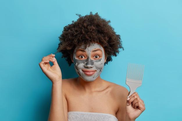 La donna dai capelli ricci cerca di pettinare i suoi sorrisi di capelli ricci applica piacevolmente la maschera di argilla subisce trattamenti per il viso avvolti in pose di asciugamano contro il muro blu