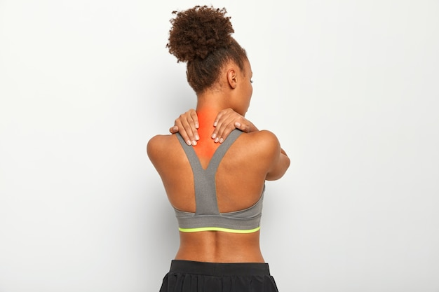 Curly haired young afro woman massages tense muscles, has pain in neck and spasm, dark skin, wears sport bra, isolated over white background