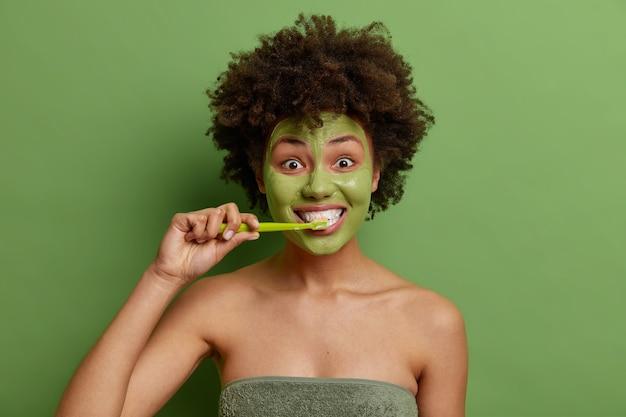 아프로 헤어 브러시 이빨을 가진 곱슬 머리 어린 소녀는 매일 위생 루틴을 거치며 생생한 녹색 벽 위에 고립 된 수건으로 싸인 건강한 피부를위한 페이셜 마스크를 적용합니다.