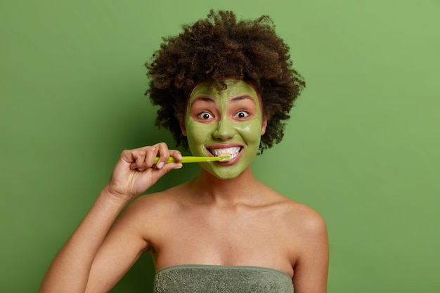 Curly haired young girl with afro hair brushes teeth undergoes daily hygiene routines applies facial mask for healthy skin wrapped in towel isolated over vivid green wall
