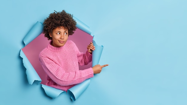 Curly haired young woman gives advice where to go indicates place for advertisement breaks through blue wall wears knitted sweater recommends something