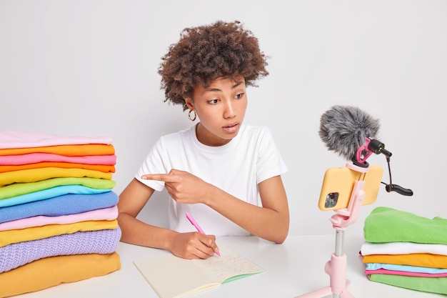 Curly haired young woman points at pile of folded clothees gives recommendations