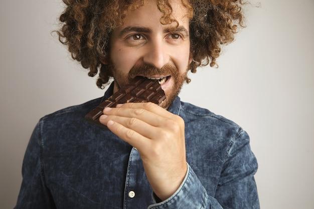 L'uomo riccio felice con la pelle sana morde la barretta di cioccolato artigianale fatta in casa, mentre sorride, isolato su bianco, indossa la camicia di jeans