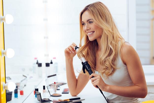 Кудрявая лучше! вид сбоку красивой молодой женщины, смотрящей на свое отражение в зеркале и использующей щипцы для завивки волос, сидя за туалетным столиком