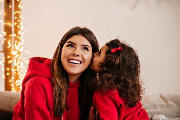 집에서 엄마 키스 곱슬 아이. 딸과 함께 여가 시간을 즐기는 젊은 어머니.