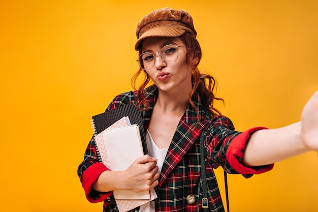 Curly lady in eyeglasses and cap blows kiss, holds notebooks and takes selfie