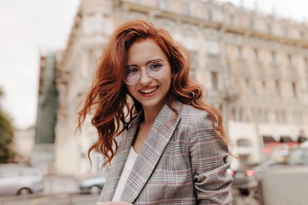 Кудрявая дама в очках улыбается и позирует на улице