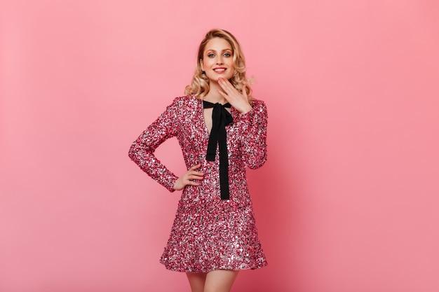ピンクの壁の正面を見て輝くドレスの巻き毛の女性