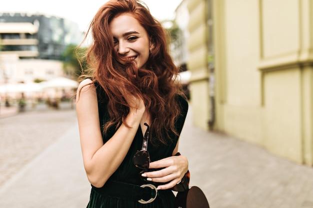 笑顔で街を歩いている巻き毛の女性