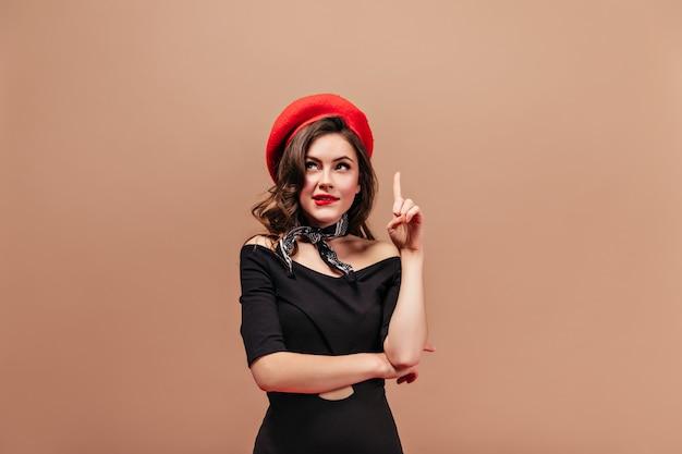 Signora riccia con labbra rosse, alzando lo sguardo pensieroso e mostrando il dito indice. ritratto di donna in berretto luminoso e abito nero.