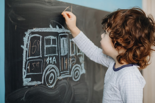 Curly little boy draws chalk on a board in his room