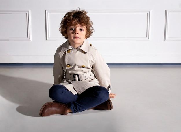 Кудрявый маленький мальчик в осеннем наряде, сидящий на полу в студии
