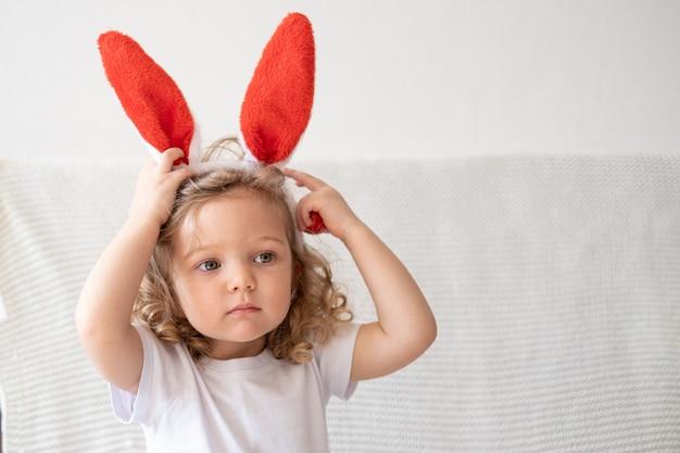 Курчавая маленькая милая кавказская девушка в ушах зайчика, сидя на софе. пасхальный.