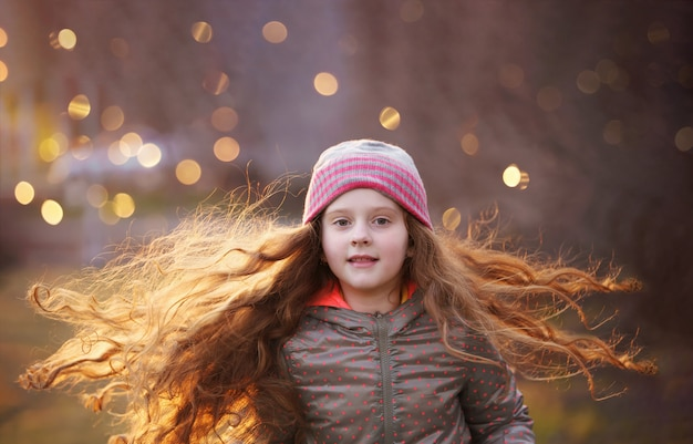 Curly little girl with flying redhead hair. freedom, healthy, lifestyle concept.