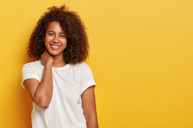 Curly lovely female touches neck, grins joyfully, has flirty look, enjoys spare time, wears casual white t shirt, talks casually with someone, expresses positive emotions isolated on yellow wall