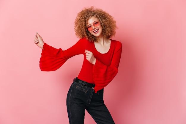Кудрявая милая женщина танцует на розовом пространстве. портрет блондинки в розовых очках, красной блузке и джинсах.
