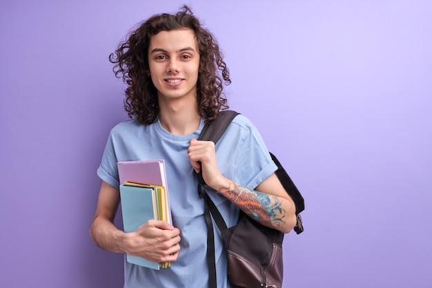カーリー男性は、大学や大学でキャマーを見て勉強を始めて幸せなカラフルな本を抱きしめています...