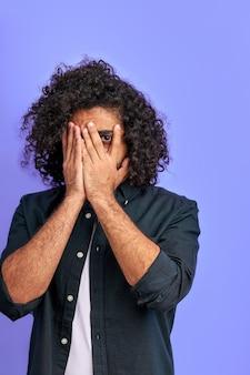 巻き毛の男性は何かに怖がって、手で顔を閉じ、片目でカメラを見て、スタジオで隔離