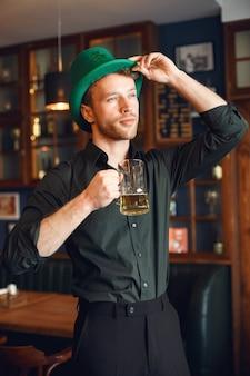 녹색 모자에 곱슬 남자. 남자는 맥주를 마신다. 남자는 술집에서 휴가를 축하합니다.