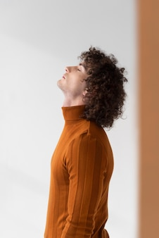 Curly man with brown blouse posing