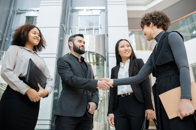 Curly manager with folder shaking hand of man while meeting with business team in office