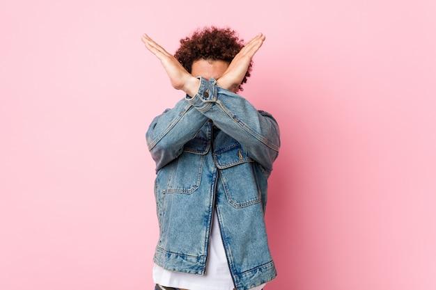 Кудрявый зрелый мужчина в джинсовой куртке на розовой стене, скрестив руки