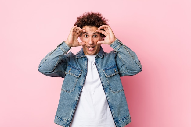 Curly mature man wearing a denim jacket against pink background keeping eyes opened to find a success opportunity.
