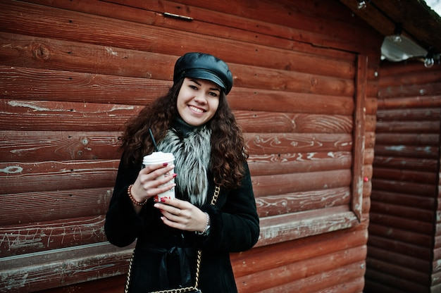 Curly mexican girl in leather cap and plastic cup of coffee at hand against wooden market.