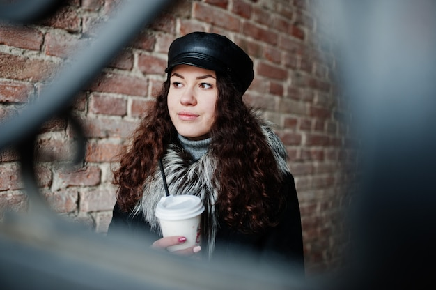 Curly mexican girl in leather cap and plastic cup of coffee at hand walking at streets of city.