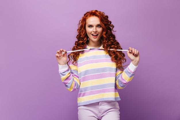 Кудрявая озорная девушка в разноцветной толстовке с капюшоном затягивает завязки на капюшоне и смотрит вперед