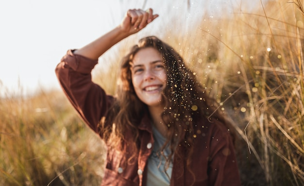 Curly model in a brown jacket smiling and throwing glitter in the air