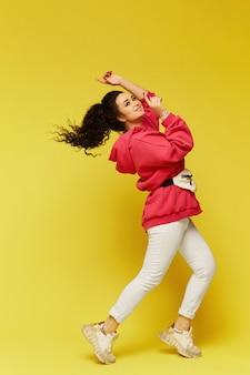 ピンクの特大のパーカーのカーリー モデルの女の子は、黄色の背景に魅力的な女性が黄色の背景に笑顔で笑みを浮かべてください。