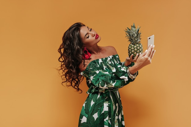 Curly modern girl with dark long hair and big lips in red earrings and printed summer dress making selfie and holding pineapple