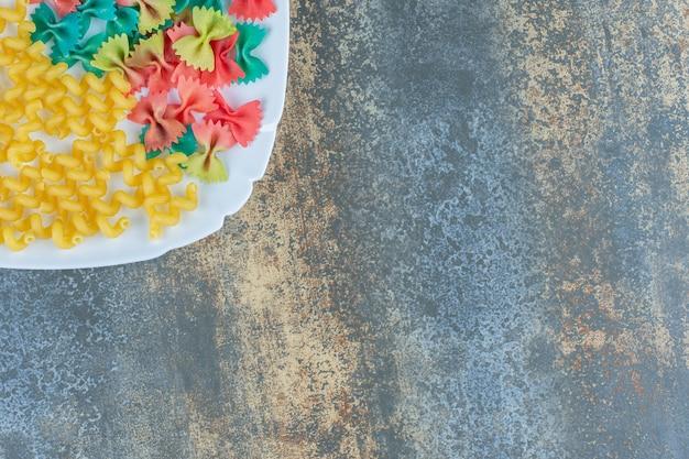 Фигурные макароны с макаронами с бабочкой на тарелке, на мраморном фоне.