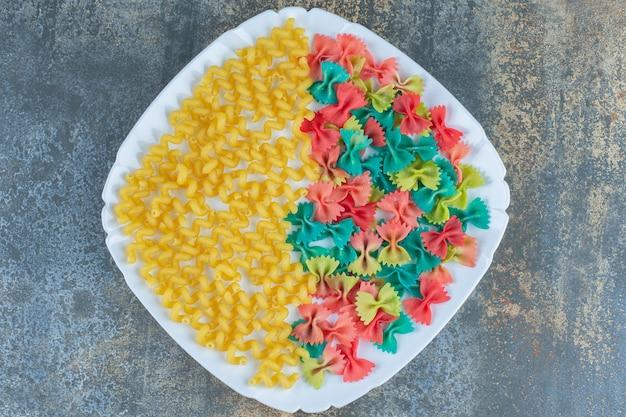 Фигурные макароны с пастами-бабочками на тарелке, на мраморной поверхности.