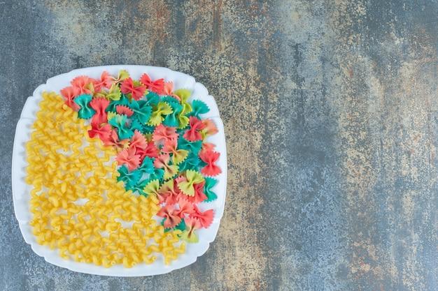 Pasta riccia con pasta di farfallino sul piatto, sulla superficie di marmo.