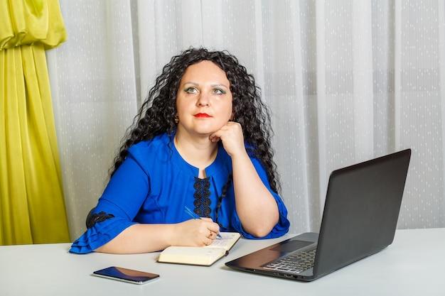 곱슬 잠겨있는 갈색 머리 여자는 사무실에서 테이블에 앉아있다. 가로 사진